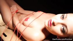 A tied up Dani frees herself so she can masturbate
