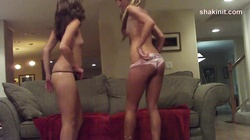 a couple of girls dancing naked on the couch